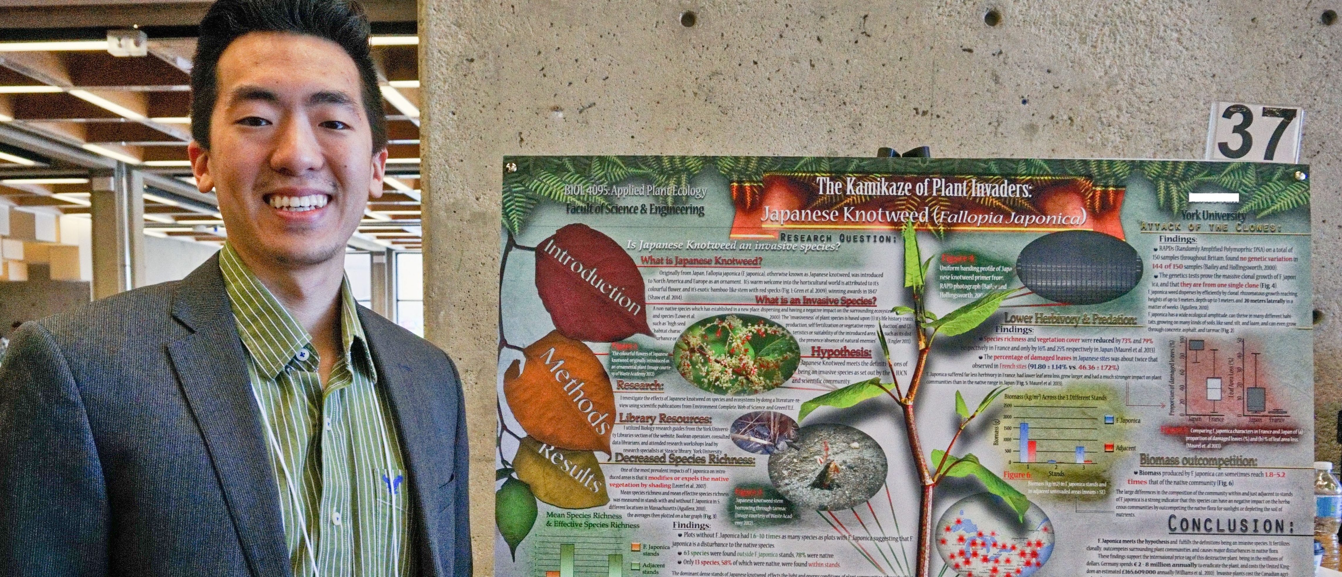 Male student standing in front of his project poster