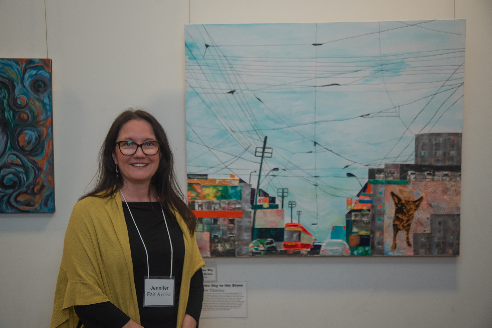Female student standing in front, on left side of her project arkwork/painting