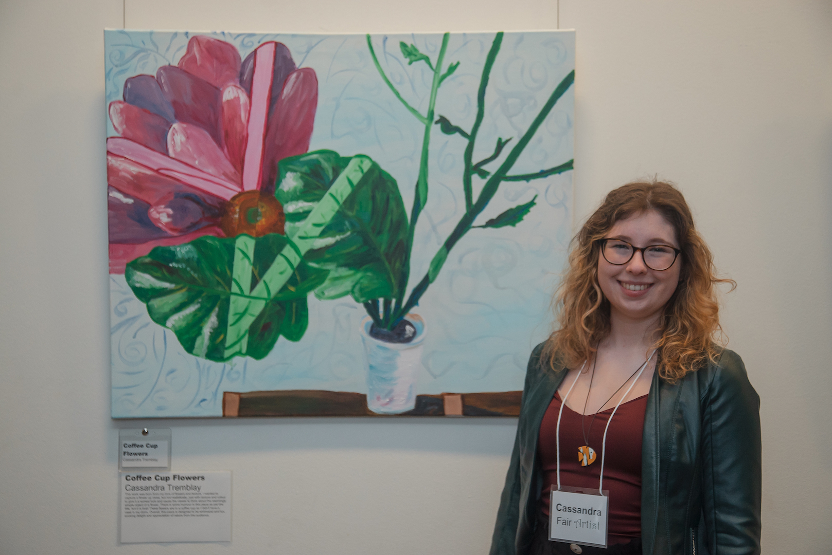 Female student standing in front, on right side of her project arkwork/painting